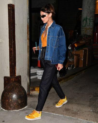Bella hadid với chiếc quần đen cá tính kết hợp với đôi giày thể thao vàng